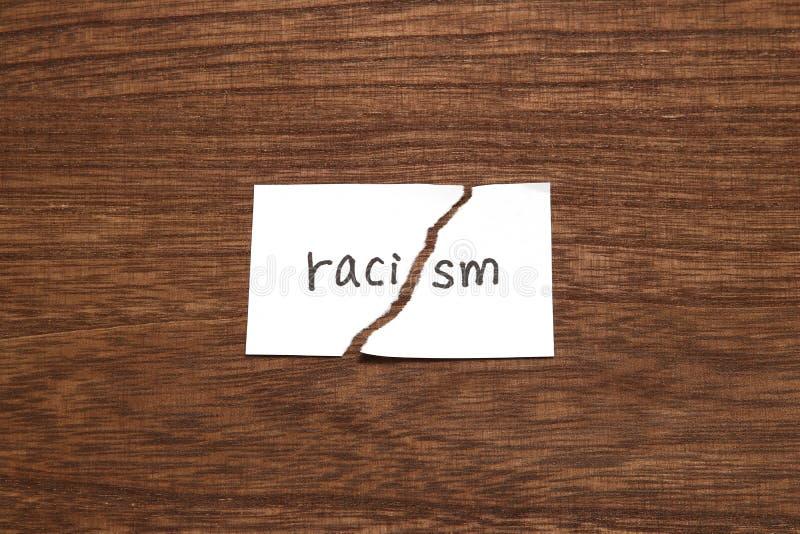 Το έγγραφο που γράφεται ως ρατσισμός είναι σχισμένο στο ξύλο Έννοια της κατάργησης της φυλετικής διάκρισης στοκ εικόνα