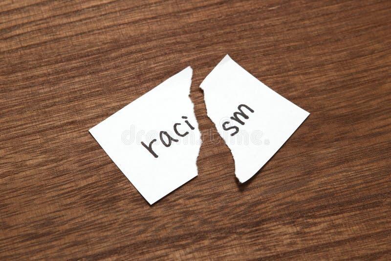 Το έγγραφο που γράφεται ως ρατσισμός είναι σχισμένο στο ξύλο Έννοια της κατάργησης της φυλετικής διάκρισης στοκ εικόνα με δικαίωμα ελεύθερης χρήσης