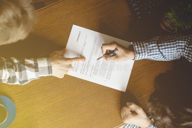 Το έγγραφο συμβάσεων, δύο άτομα υπογράφει το έγγραφο στο γραφείο μια τονισμένη εξασθενισμένη εικόνα στοκ εικόνα