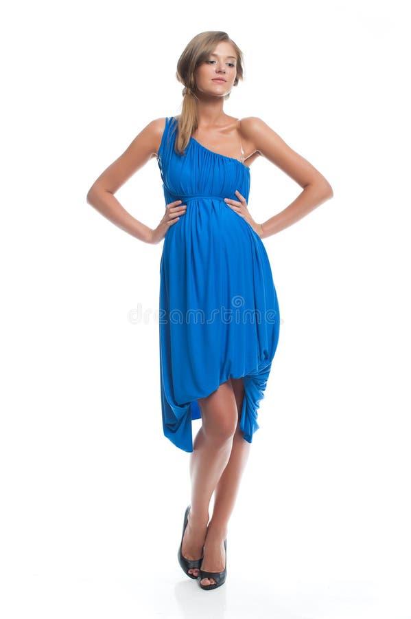 Το έγκυο ελκυστικό λεπτό πρότυπο σε ένα μπλε φόρεμα σε ένα λευκό απομόνωσε την τοποθέτηση υποβάθρου Ενδύματα βραδιού για τις εγκύ στοκ εικόνα