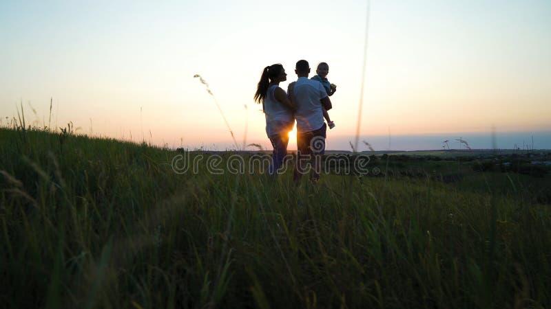 Το έγκυο ζεύγος με την κόρη μικρών παιδιών έχει τον ελεύθερο χρόνο υπαίθρια στο ηλιοβασίλεμα στοκ εικόνα