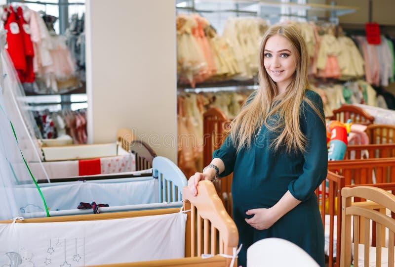 Το έγκυο κορίτσι επιλέγει μια κούνια μωρών στο κατάστημα στοκ εικόνα με δικαίωμα ελεύθερης χρήσης