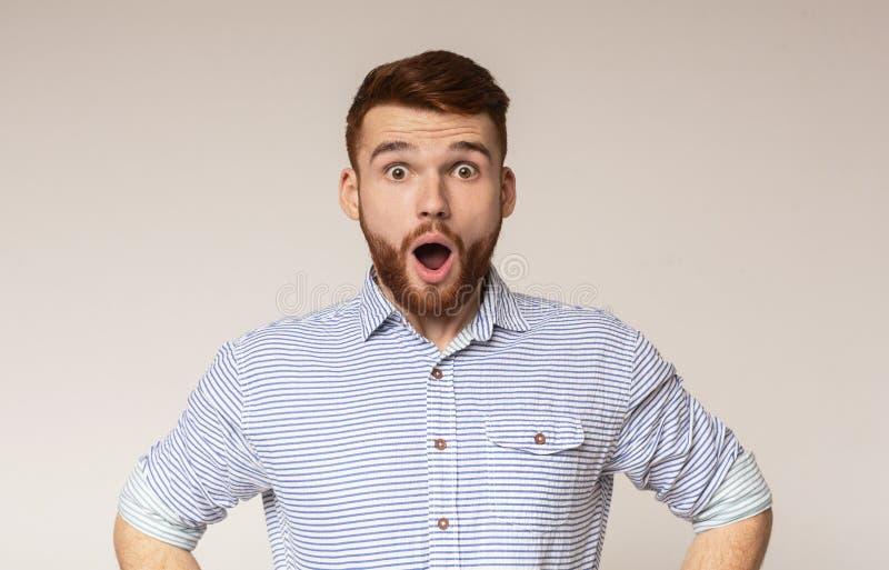 Το έκπληκτο άτομο με συγκλονισμένος κοιτάζει στο υπόβαθρο στούντιο στοκ φωτογραφία με δικαίωμα ελεύθερης χρήσης