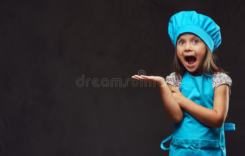Το έκπληκτο μικρό κορίτσι έντυσε στην μπλε τοποθέτηση μαγείρων σε ένα στούντιο στο σκοτεινό κατασκευασμένο υπόβαθρο στοκ φωτογραφίες με δικαίωμα ελεύθερης χρήσης