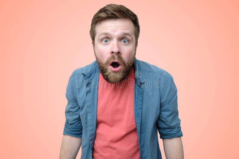 Το έκπληκτο, συναισθηματικό γενειοφόρο άτομο άνοιξε το στόμα του ευρέως με το amazement σε ένα υπόβαθρο κοραλλιών στοκ εικόνες