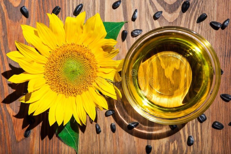 Το έλαιο και ο κίτρινος ηλίανθος στο γυαλί κυλούν και σπόροι γύρω στο ξύλινο υπόβαθρο στοκ εικόνα με δικαίωμα ελεύθερης χρήσης