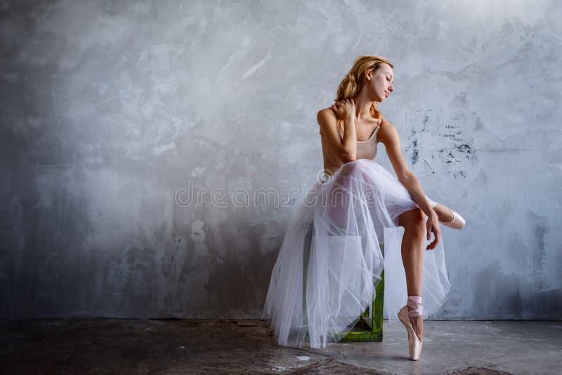 Το έξοχο λεπτό ballerina σε ένα μαύρο φόρεμα θέτει στο στούντιο στοκ εικόνες