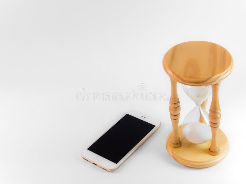Το έξυπνες τηλέφωνο και η κλεψύδρα απομονώνουν στο λευκό στοκ φωτογραφία