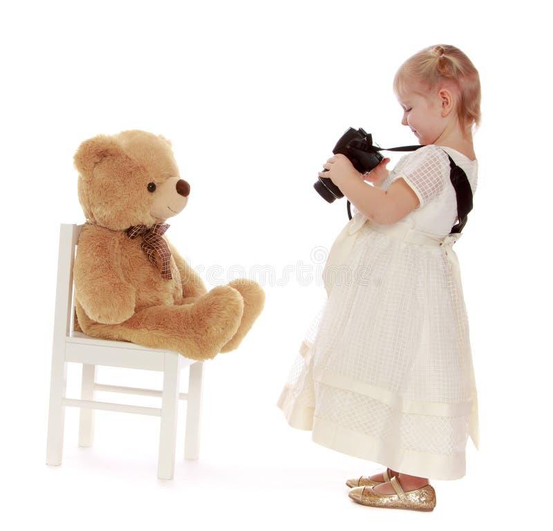 Το έξυπνο μικρό κορίτσι φωτογράφισε τη συμπάθειά του teddy στοκ εικόνες με δικαίωμα ελεύθερης χρήσης