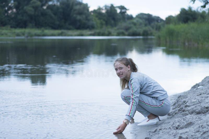 Το έφηβη κάθεται στη λίμνη στοκ φωτογραφίες