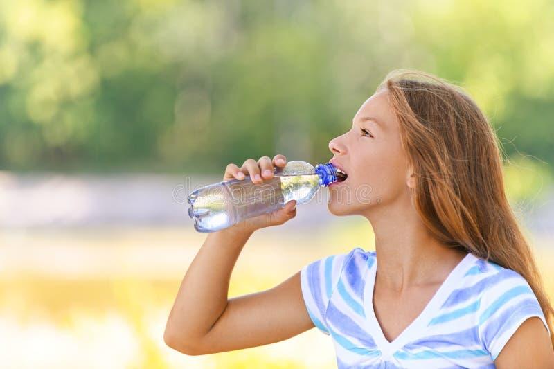 Το έφηβη πίνει το ύδωρ από στοκ εικόνες