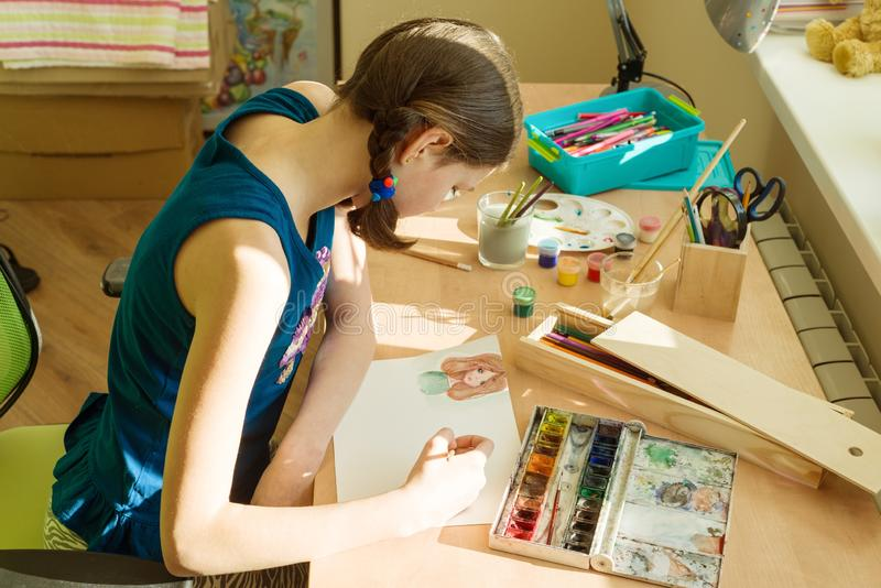 Το έφηβη συμμετέχει στο σπίτι στη δημιουργικότητα, σύρει το watercolor σε έναν πίνακα στο δωμάτιο στοκ φωτογραφίες