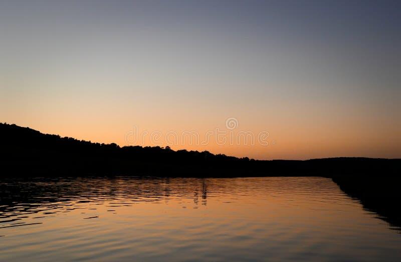 Το ήρεμο, γαλήνιο νερό λιμνών απεικονίζει το χρυσό φως σούρουπου στοκ εικόνα