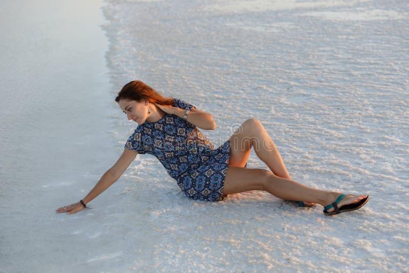 Το ήρεμο κορίτσι που απολαμβάνει τον ήλιο, κάθεται στο έδαφος που καλύπτεται με το άλας κοντά στη λίμνη στοκ εικόνα με δικαίωμα ελεύθερης χρήσης