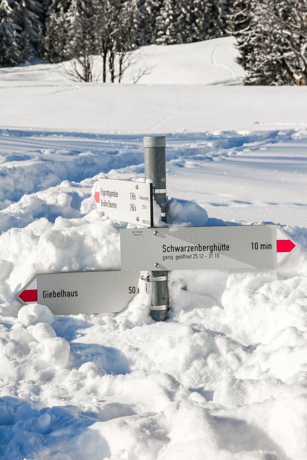Το ίχνος πεζοπορίας καθοδηγεί τα ραβδιά από το βαθύ χιόνι στο χειμερινό τοπίο βουνών την ηλιόλουστη ημέρα Allgau, Βαυαρία, Γερμαν στοκ εικόνα