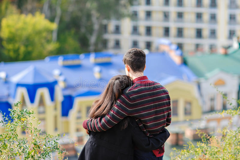 Το αγαπώντας ζεύγος αγκαλιάζει το ένα το άλλο και εξετάζει την πόλη στοκ εικόνες