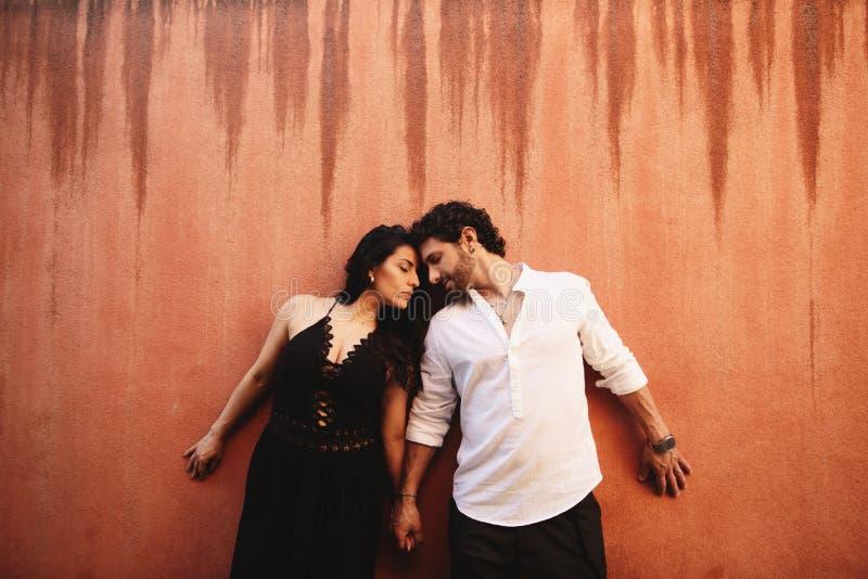 Το αγαπώντας ζεύγος κρατά ήπια τα χέρια, που κλίνουν ο ένας εναντίον του άλλου Πίσω από τους είναι το υπόβαθρο ενός τοίχου τερακό στοκ εικόνες
