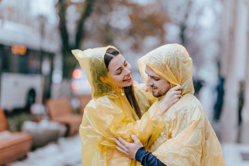 Το αγαπώντας ζεύγος, ο τύπος και η φίλη του που ντύνονται στα κίτρινα αδιάβροχα αγκαλιάζουν στην οδό στη βροχή στοκ εικόνες με δικαίωμα ελεύθερης χρήσης