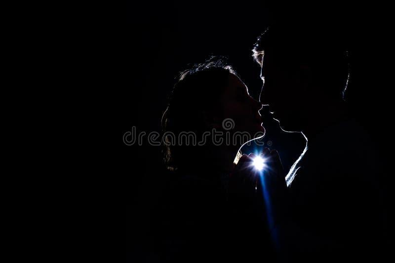 Το αγαπώντας ζεύγος που στέκονται στο σκοτάδι, και η σκιαγραφία της ανάβουν τις ακτίνες στοκ φωτογραφία