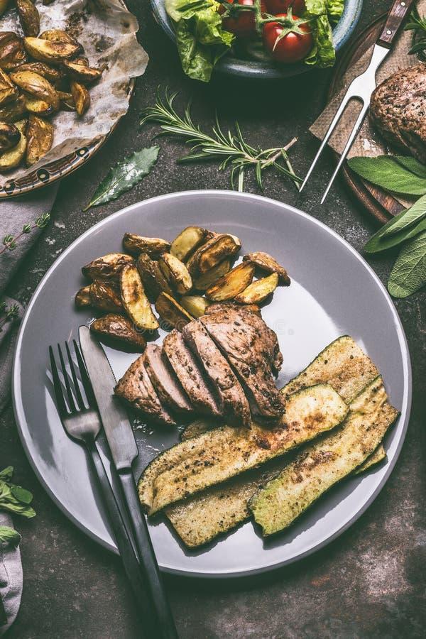 Το αγροτικό γεύμα με το τηγανισμένο τεμαχισμένο κρέας, τις ψημένα πατάτες και τα λαχανικά, εξυπηρέτησε στο πιάτο με τα μαχαιροπήρ στοκ εικόνα με δικαίωμα ελεύθερης χρήσης