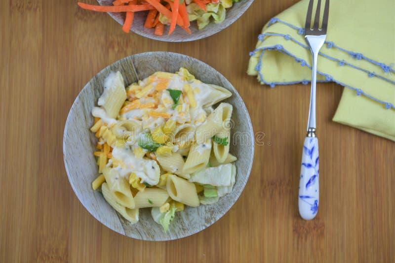 Το αγροτικό επίπεδο βάζει με το κύπελλο της σαλάτας ζυμαρικών τυριών σε έναν ξύλινο πίνακα ή ένα γραφείο στοκ εικόνες με δικαίωμα ελεύθερης χρήσης