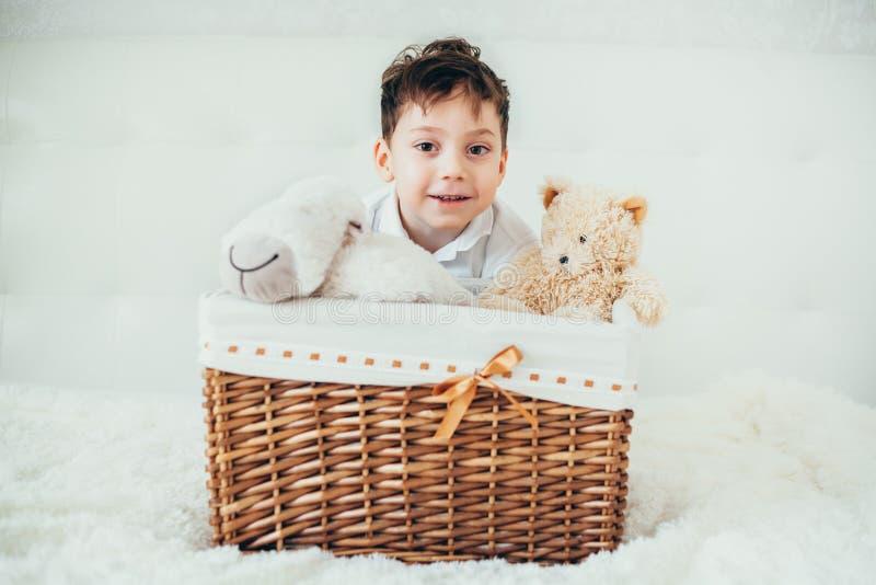 Το αγόρι έκρυψε πίσω από ένα καλάθι με τα μαλακά παιχνίδια στοκ εικόνα