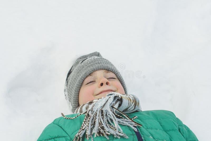 Το αγόρι ένα καπέλο, μαντίλι και ένα πράσινο σακάκι βρίσκεται στην πλάτη του στο χιόνι Πορτρέτο Κινηματογράφηση σε πρώτο πλάνο ο  στοκ εικόνα με δικαίωμα ελεύθερης χρήσης