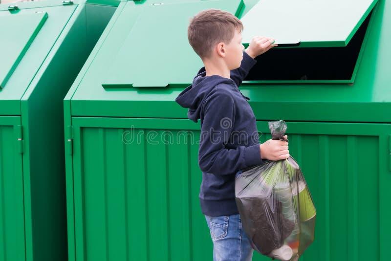 Το αγόρι ήρθε στο δοχείο απορριμμάτων με μια συσκευασία των αποβλήτων στοκ εικόνα