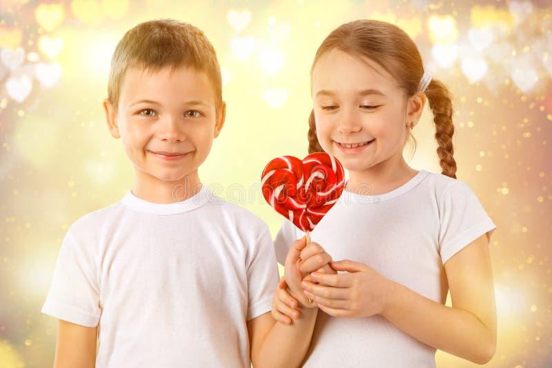 Το αγόρι δίνει σε μια μικρή καραμέλα κοριτσιών το κόκκινο lollipop στη μορφή καρδιών βαλεντίνος ημέρας s Αγάπη παιδιών στοκ εικόνα με δικαίωμα ελεύθερης χρήσης