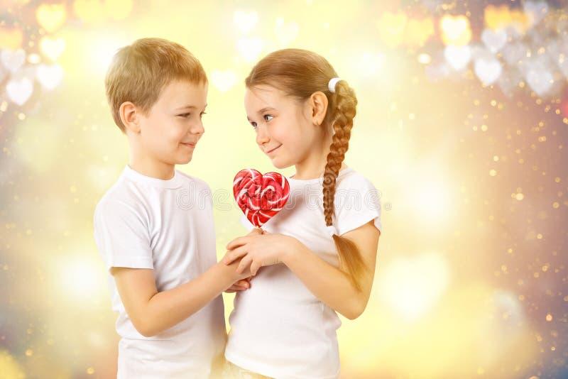 Το αγόρι δίνει σε μια μικρή καραμέλα κοριτσιών το κόκκινο lollipop στη μορφή καρδιών βαλεντίνος ημέρας s στοκ εικόνες