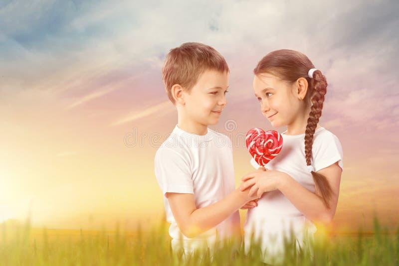 Το αγόρι δίνει σε μια μικρή καραμέλα κοριτσιών το κόκκινο lollipop στη μορφή καρδιών στον τομέα ηλιοβασιλέματος βαλεντίνος ημέρας στοκ φωτογραφία