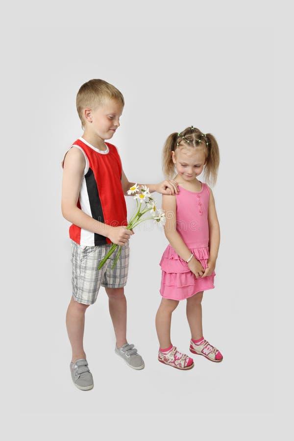 Το αγόρι δίνει την ανθοδέσμη κοριτσιών των μαργαριτών σε γκρίζο στοκ φωτογραφίες