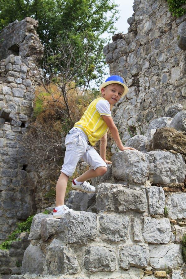 το αγόρι αναρριχείται στις καταστροφές ενός αρχαίου κτηρίου στοκ φωτογραφίες
