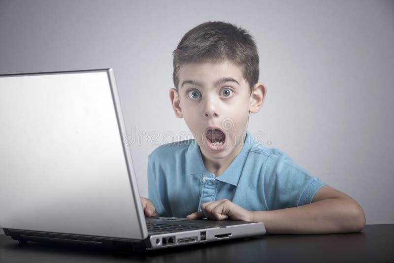 Το αγόρι αντιδρά χρησιμοποιώντας ένα lap-top στοκ εικόνα