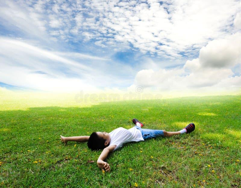 Το αγόρι βάζει στη χλόη αισθάνεται ότι χαλαρώστε στοκ εικόνα με δικαίωμα ελεύθερης χρήσης