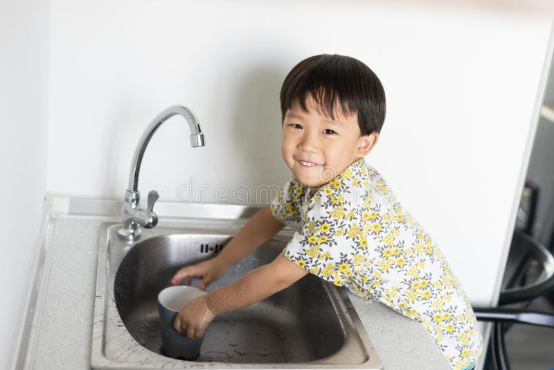 Το αγόρι βοηθά τη μητέρα για να κάνει τα οικιακά με το πλύσιμο ενός γυα στοκ φωτογραφίες με δικαίωμα ελεύθερης χρήσης