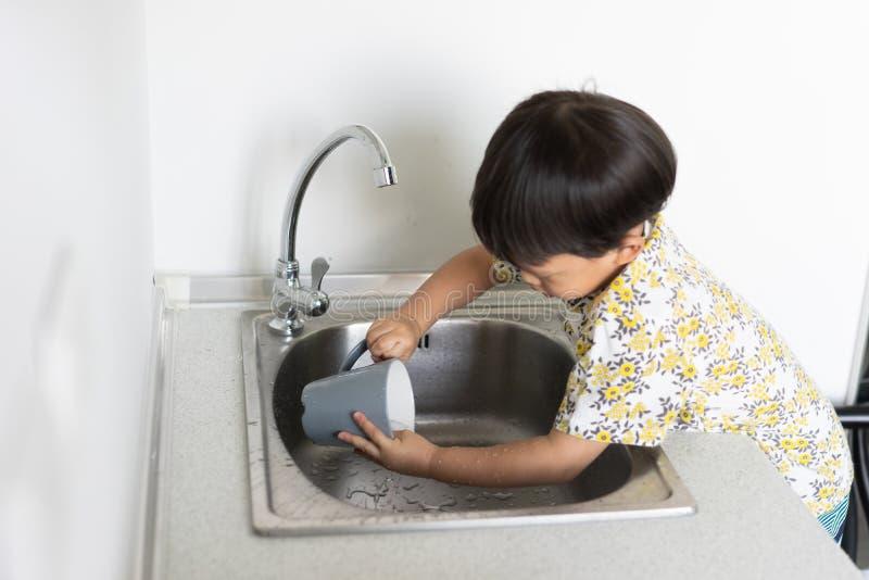 Το αγόρι βοηθά τη μητέρα για να κάνει τα οικιακά με το πλύσιμο ενός γυα στοκ φωτογραφία με δικαίωμα ελεύθερης χρήσης