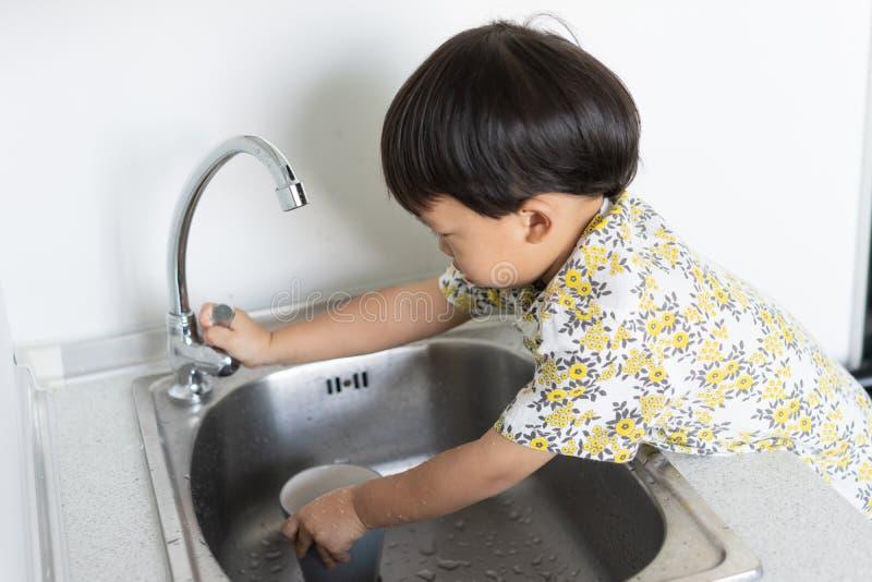 Το αγόρι βοηθά τη μητέρα για να κάνει τα οικιακά με το πλύσιμο ενός γυα στοκ εικόνες