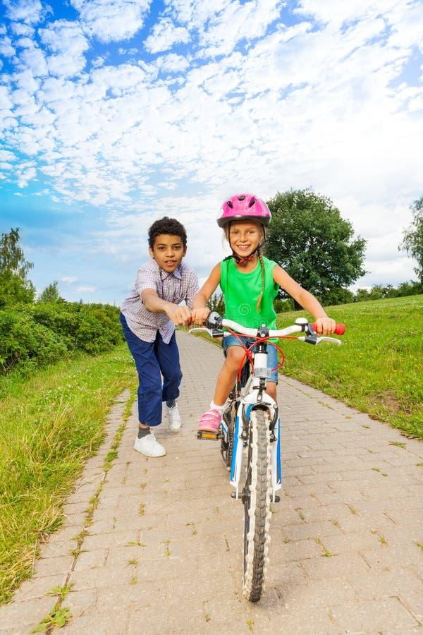 Το αγόρι βοηθά το κορίτσι για να οδηγήσει το ποδήλατο και κρατά handle-bar στοκ φωτογραφία