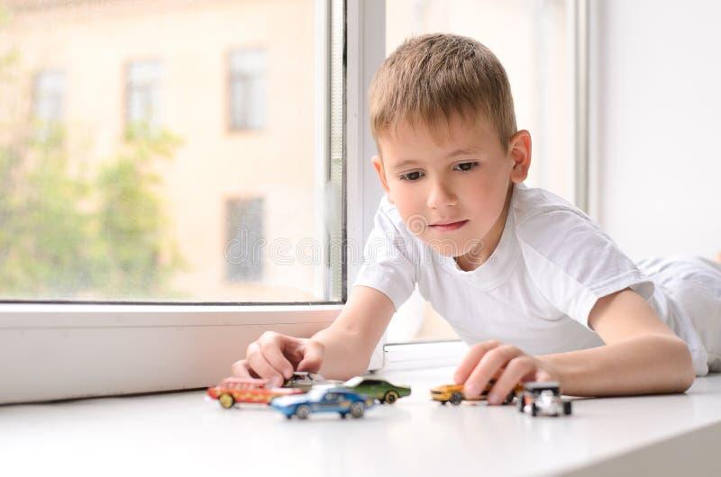 το αγόρι βρίσκεται και παίζοντας στο windowsill στοκ εικόνα