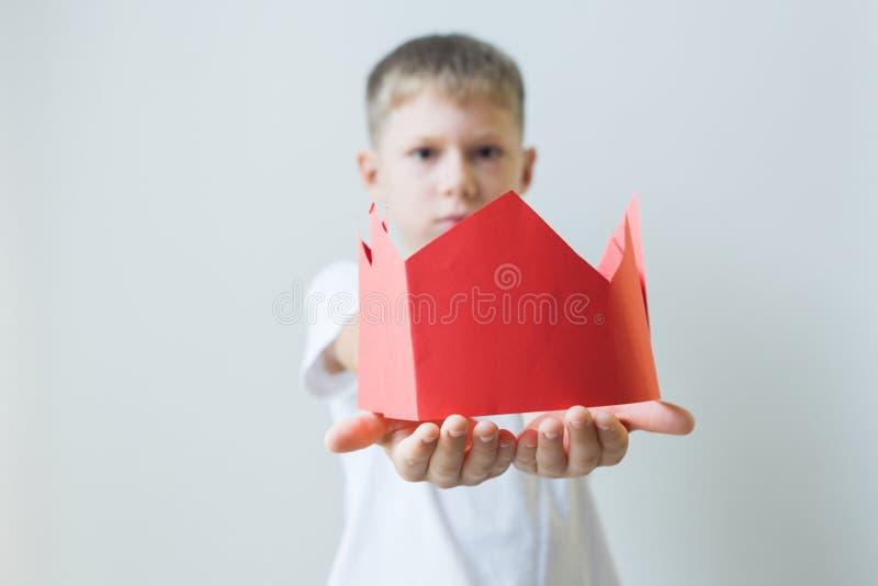 Το αγόρι δίνει μια κόκκινη πλαστή κορώνα εγγράφου Για να δώσουν τις θέσεις στοκ εικόνες