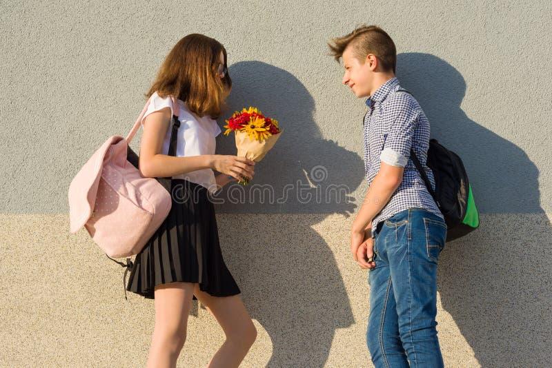 Το αγόρι δίνει την ανθοδέσμη κοριτσιών των λουλουδιών Υπαίθριο πορτρέτο των εφήβων ζευγών στοκ εικόνες