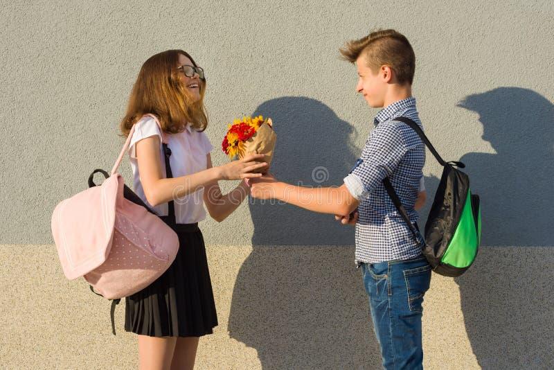 Το αγόρι δίνει την ανθοδέσμη κοριτσιών των λουλουδιών Υπαίθριο πορτρέτο των εφήβων ζευγών στοκ εικόνα με δικαίωμα ελεύθερης χρήσης
