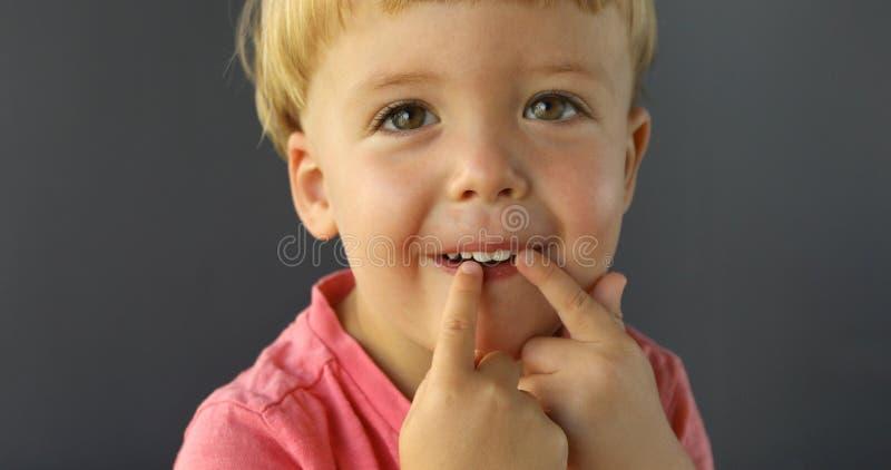 Το αγόρι δείχνει τα δάχτυλα και των δύο χεριών του στα δόντια του στοκ εικόνες