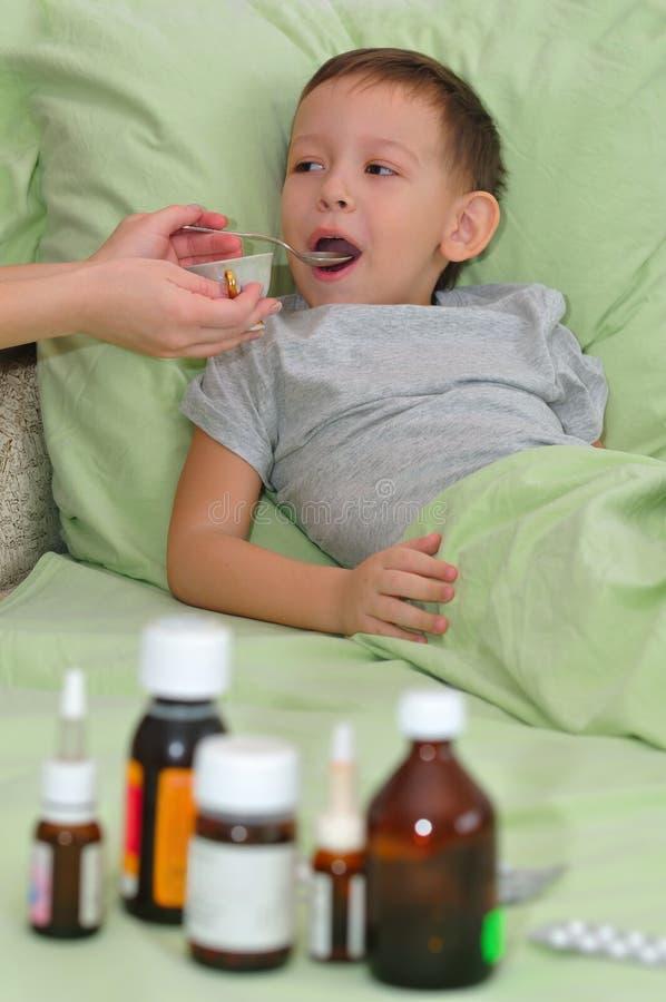 Το αγόρι είναι άρρωστο και στο κρεβάτι. Το Mom δίνει το σιρόπι. στοκ φωτογραφία με δικαίωμα ελεύθερης χρήσης