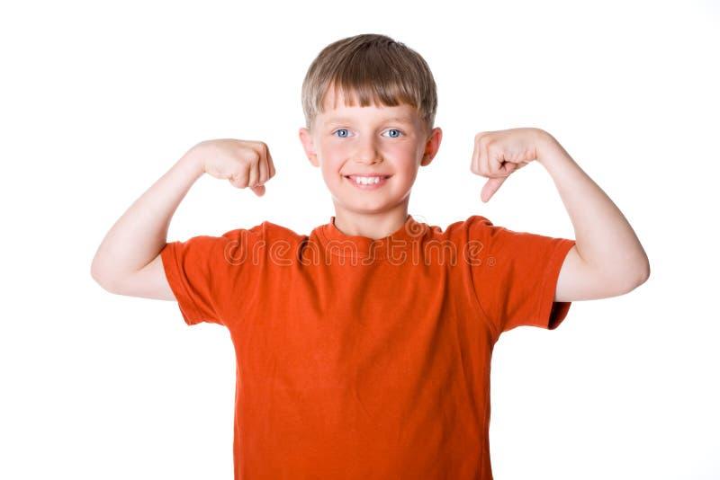 Το αγόρι εμφανίζει μυς του στοκ φωτογραφία