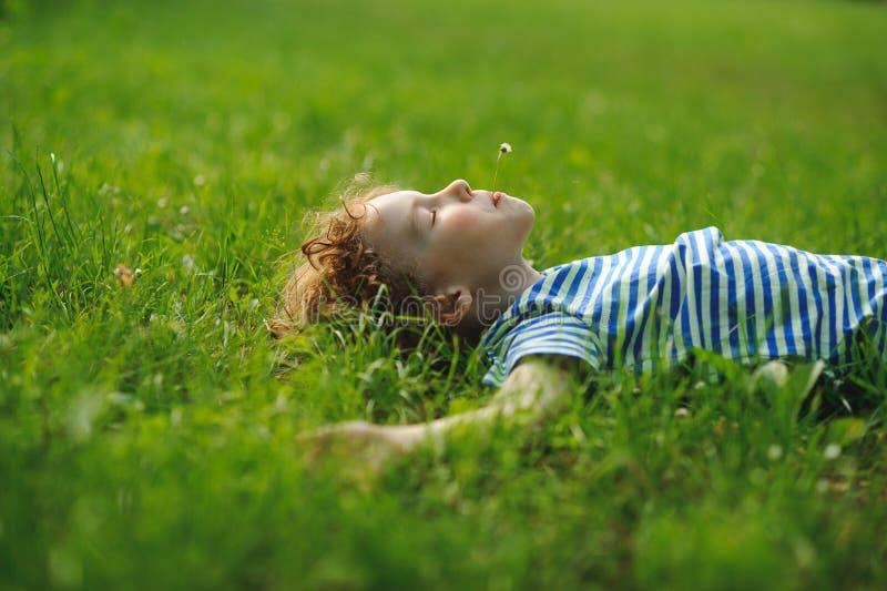 Το αγόρι 8-9 ετών βρίσκεται σε μια πλάτη στην πυκνή πράσινη χλόη στοκ εικόνες με δικαίωμα ελεύθερης χρήσης