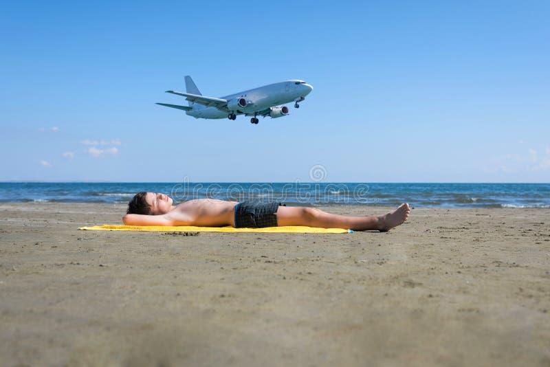 Το αγόρι εφήβων βρίσκεται στην κίτρινη πετσέτα και κάνει ηλιοθεραπεία στην παραλία κάτω από τα προσγειωμένος αεροπλάνα Ταξίδι σε  στοκ φωτογραφίες