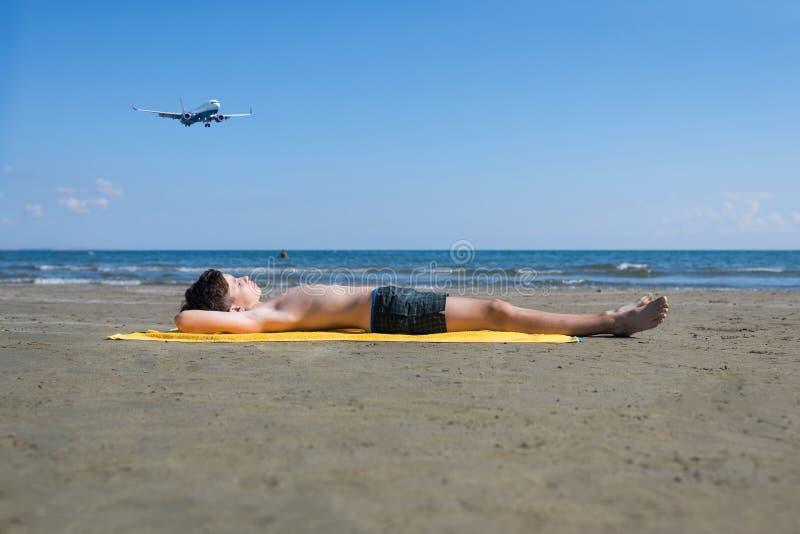 Το αγόρι εφήβων βρίσκεται στην κίτρινη πετσέτα και κάνει ηλιοθεραπεία στην παραλία κάτω από τα προσγειωμένος αεροπλάνα Ταξίδι σε  στοκ εικόνα