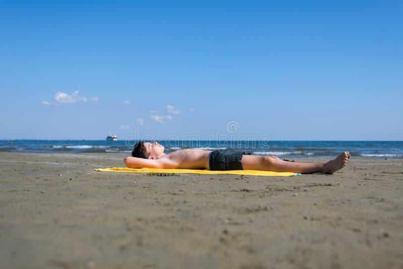Το αγόρι εφήβων βρίσκεται στην κίτρινη πετσέτα και κάνει ηλιοθεραπεία στην παραλία στοκ εικόνα με δικαίωμα ελεύθερης χρήσης